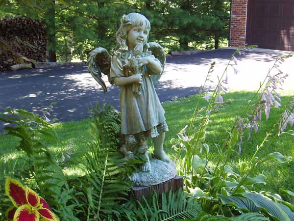 This Smiling Little Girl Angel Statue Stands Up On A Block To Get Above The  Ferns And Coleus And Hostas.